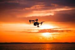 与遥控的Quadrocopter寄生虫 反对colorfull日落的黑暗的剪影 软绵绵地集中 被定调子的图象 图库摄影