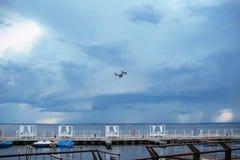 与遥控的Quadrocopter寄生虫 雷云风暴,阴沉 在湖的风雨如磐的天空 库存照片
