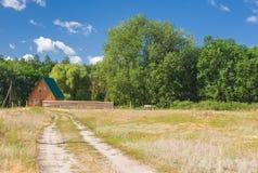 与遥远的房子的风景在森林边缘 免版税库存照片