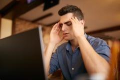 与遭受头疼偏头痛的闭合的眼睛的严肃的沮丧的商人在工作场所,按摩寺庙 图库摄影