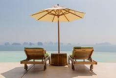 与遮阳伞和太阳床的无限水池在海边 免版税库存图片