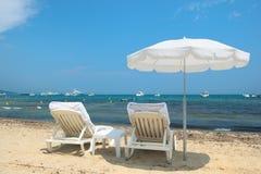 与遮阳伞和床的海滩 免版税库存照片