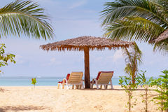 与遮阳伞和轻便折叠躺椅的海滩风景 库存图片