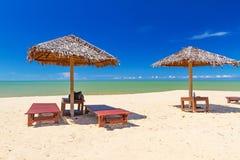 与遮阳伞和轻便折叠躺椅的热带海滩风景 库存图片