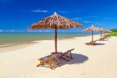 与遮阳伞和轻便折叠躺椅的热带海滩风景 免版税库存照片