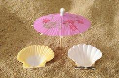 与遮阳伞的壳在作为标志的海滩为假日 免版税图库摄影