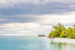 与遮阳伞的热带海滩日落在马尔代夫海岛 库存照片