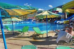 与遮阳伞的细节和轻便折叠躺椅和游泳池 免版税库存图片