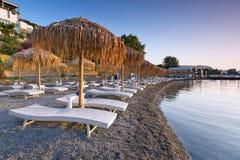 与遮阳伞的Sunbeds在Mirabello海湾 免版税库存照片