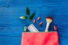 与避孕药的化妆袋子在蓝色桌背景顶视图copyspace 库存图片