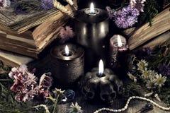 与邪恶的黑蜡烛、古色古香的书和草本的静物画在神秘的光 免版税库存图片