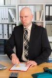 与邮票的商人在办公室看起来滑稽对 库存图片