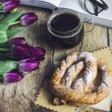 与郁金香、书、咖啡和椒盐脆饼的静物画在木背景 图库摄影