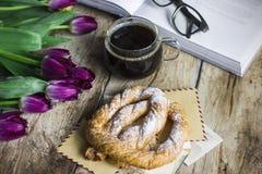 与郁金香、书、咖啡和椒盐脆饼的静物画在老背景 免版税图库摄影