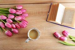 与郁金香和阅读书-在w的顶视图的早晨咖啡 免版税图库摄影