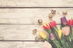 与郁金香和鸡蛋的白色木复活节背景,被定调子 免版税库存图片