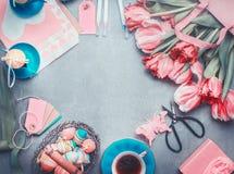 与郁金香束、鸡蛋和装饰的复活节背景在淡色 免版税库存图片