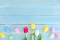 与郁金香的五颜六色的复活节彩蛋在蓝色木背景开花 免版税图库摄影