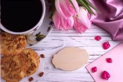 与郁金香的华伦泰` s天典雅的静物画开花杯子在白色木背景的coffe蛋白软糖红色心脏形状标志 库存照片