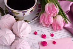 与郁金香的华伦泰` s天典雅的静物画开花杯子在白色木背景的coffe蛋白软糖红色心脏形状标志 图库摄影