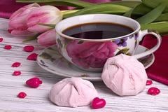 与郁金香的华伦泰` s天典雅的静物画开花杯子在白色木背景的coffe蛋白软糖红色心脏形状标志 免版税图库摄影