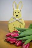 与郁金香的复活节兔子,黄色背景 库存照片