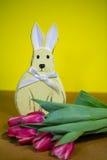 与郁金香的复活节兔子,黄色背景 免版税库存照片