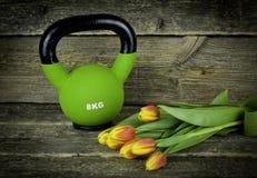 与郁金香的绿色kettlebells在土气木桌上 库存图片