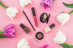 与郁金香花和化妆用品的秀丽构成在桃红色背景 顶视图 平的位置 家庭女性书桌 免版税库存图片