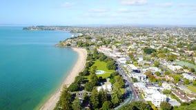 与郊区住宅区的晴朗的海滩背景的 奥克兰新西兰 免版税库存图片