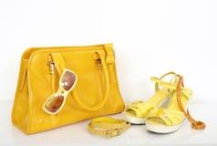 与配比的凉鞋和辅助部件的夏天黄色袋子 库存照片