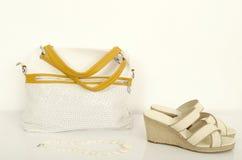 与配比的楔子凉鞋的白色和黄色袋子 库存照片