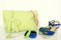 与配比的辅助部件和逗人喜爱的凉鞋的大霓虹绿色袋子 图库摄影