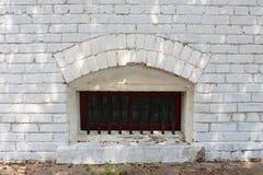 与酒吧的小被成拱形的地下室窗口在一个白色砖墙 免版税库存照片