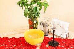 与酒杯、板材和花的静物画在厨房用桌上 免版税库存照片