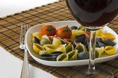 与酒杯的意大利多色意大利面食 库存图片