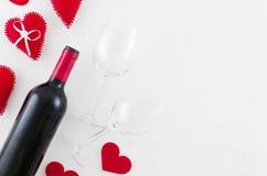 与酒瓶、毛毡心脏和葡萄酒杯的平的被放置的情人节贺卡在白色背景 顶视图与 库存图片
