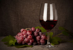 与酒瓶、玻璃和葡萄的静物画 免版税库存照片