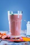 与酸奶和红萝卜切片在木桌上,关闭的红萝卜汁 库存照片