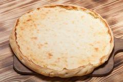 与酸奶干酪vatrushka的新鲜的饼在新的被烧的木背景 免版税库存图片