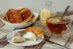 与酸性稀奶油和一杯茶的薄煎饼早餐 库存照片