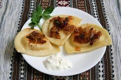 与酸性稀奶油和油煎的葱的Pierogis 图库摄影