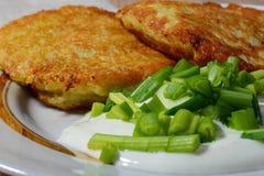 与酸性稀奶油和葱的自创油煎的土豆薄烤饼 库存照片