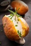 与酸性稀奶油的切的被烘烤的带皮烤的土豆 图库摄影