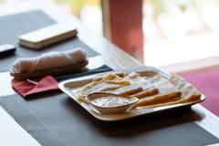与酸性稀奶油的薄煎饼在桌上的白方块板材 免版税图库摄影