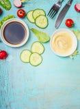 与醋和芥末选矿的鲜美沙拉在轻的破旧的别致的蓝色背景,顶视图的准备和利器 免版税库存图片