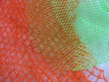 与醒目的明亮的橙色和绿色渔网样式的织地不很细抽象背景 图库摄影