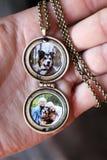与里面孩子和爱犬照片的妇女的手藏品古色古香的小盒  免版税图库摄影
