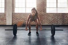 与重量酒吧的女性执行的deadlift锻炼 免版税库存图片