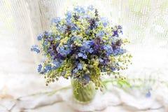与野花的美丽的明亮的蓝色和白色花束在窗台在阳光下 与bokeh的特写镜头照片 免版税库存照片